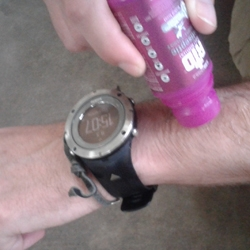 A man wearing a Suunto sports watch applies RID insect repellent roll-on to his arm