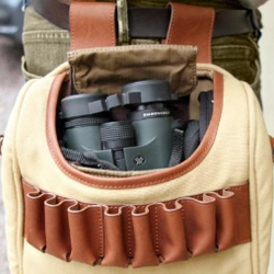 An open leather and canvas satchel containing a pair of green Vortex binoculars