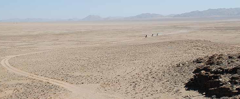 Three vehicles driving on a distant desert road in a barren landscape