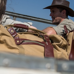 A man wearing a hat sitting in the front seat of a safari vehicle with a canvas duffel bag in the back