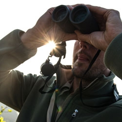 A man looking through a pair of binoculars