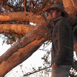 A man wearing a safari hat and fleece stares off into the distance with a tree behind him