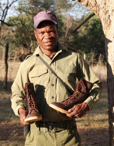 Make a contribution to conservation with every purchase. APU member, Misheck, receives his brand new pair of boots!