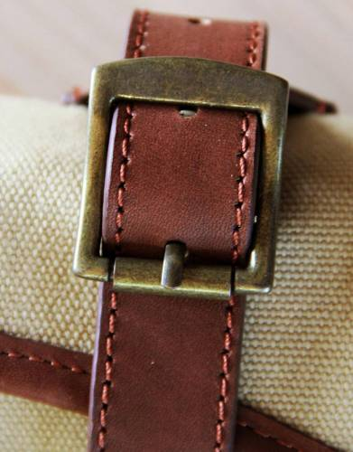 The leather straps and brass buckles secure the rolled up washbag for travelling
