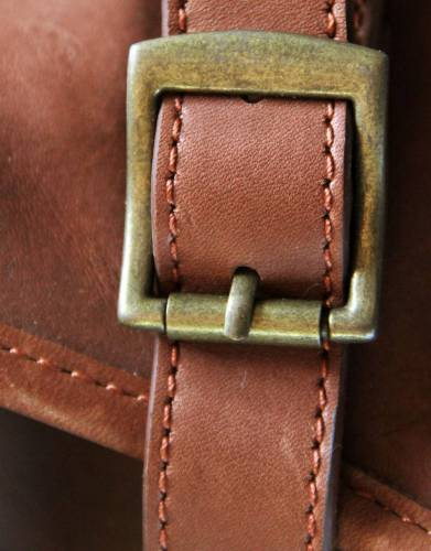 The straps and brass buckles secure the rolled up washbag for travelling