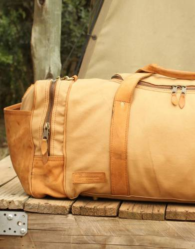 This lined bag features large end pockets and a detachable leather shoulder strap for your travel convenience.