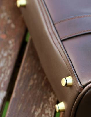The Business Bag has brass feet to keep your bag upright when you set it down and to prevent scuffing on the underside of the bag.