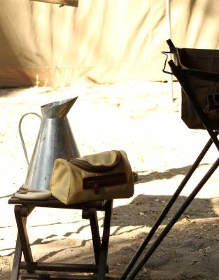 Capture the sense of vintage safaris with a canvas and leather washbag - pictured here in camp in the Okavango Delta.