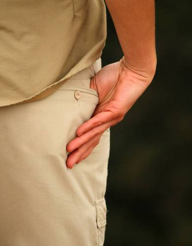 The single back pocket with button closure complements the overall design of the trousers.
