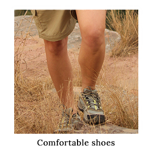 A woman's legs with a pair of Merrell Safari Walking Shoes stepping over a rock in the grass on safari in Africa