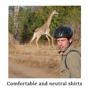 Man in a safari shirt in technical fabric and a bike helmet with a running giraffe on a cycle safari in North Luangwa, Zambia