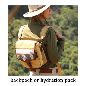 An outdoor woman wearing a safari hat, safari shirt, and carrying a safari backpack with a lion flap on a walking safari