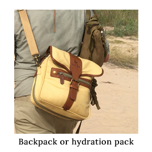 Canvas and leather satchel with brass studs and zip being carried as a day pack on a walking safari in Africa