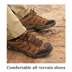 The feet of a man in safari trousers wearing the Merrell Moab Ventilator Shoes on a trail on safari in Africa