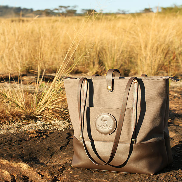 A brown canvas and leather tote bag on rocks in Africa with dry savannah grass in the background.
