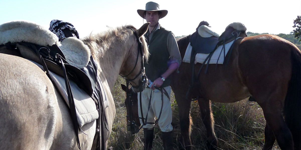 A man dressed in safari clothing holding the reins of two horses on a horse safari in St Lucia, South Africa