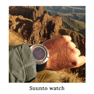 A man's wrist with the Suunto fitness GPS watch in front of a mountain view for time, GPS, and fitness stats on safari