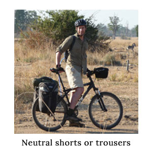 Man in a safari shirt and zip-off safari trousers which have been converted into safari shorts on a cycle safari with a zebra