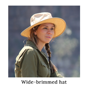 A woman on a walking safari wearing a wide-brimmed safari hat for sun protection and a safari-friendly, neutral shirt