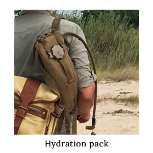 The back of a man carrying a canvas and leather safari satchel and a hydration pack through the bush on safari in Africa