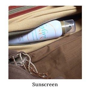 A bottle of SafariSUN sunscreen spray in a canvas and leather bag – packed for sun protection on safari in Africa