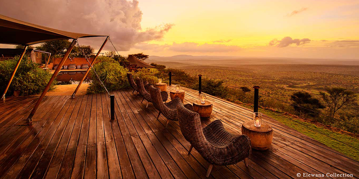Wooden deck with wicker chairs and candles overlooking a view of the Kenyan savanna at Loisaba Tented Camp