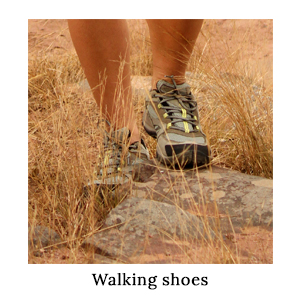 You need to pack comfortable shoes for a walking safari. A woman stepping over a rock in Merrell Safari Walking Shoes