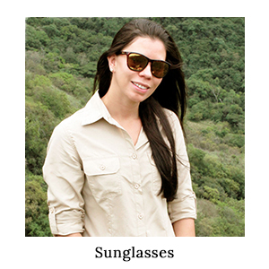 A woman in a safari shirt and Bolle sunglasses for sun protection, standing in the bush on safari in Africa