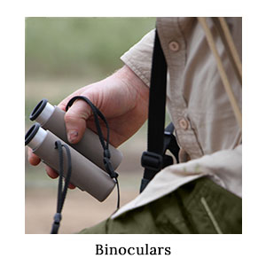 Man in safari clothing holding a pair of Swarovski CL10x25 Pocket Binoculars in his hand while game-viewing on a cycle safari