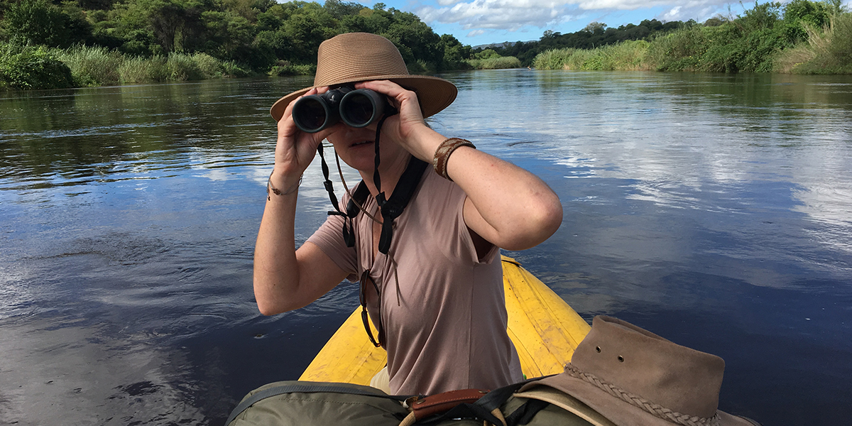 Woman in a hat and safari T-shirt looking behind her with a pair of Swarovski 10x42 binoculars on a boat on the Kafue River
