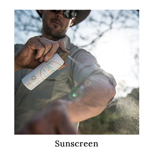 A man in a safari shirt, hat, and sunglasses spraying his arm with SafariSUN sunscreen for sun protection on safari in Africa