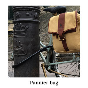 The rear wheel of a bicycle with a canvas and leather safari pannier bag attached to it, chained to a lamp post