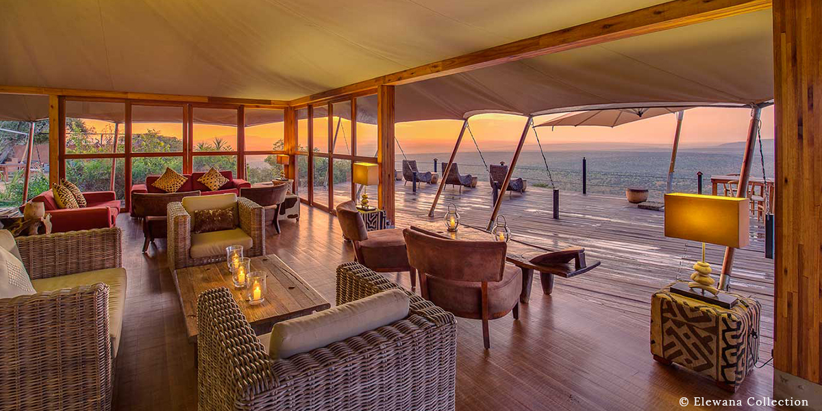 Interior view of couches and furniture across the wooden deck and the plains beyond at Loisaba Tented Camp