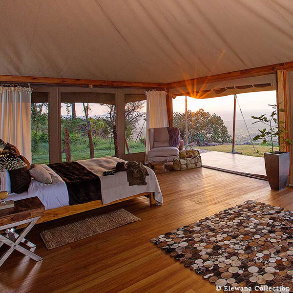 The interior of one of the luxury safari tents with a bed and view over the bush at Loisaba Tented Camp in Kenya