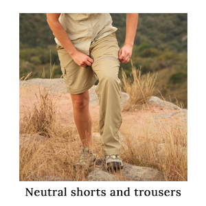 A woman converting her zip-off trousers into a pair of safari shorts when the weather gets warm on a walking safari in Africa