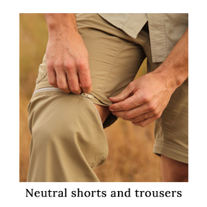 A man unzipping his zip-off safari trousers and converting them into a pair of shorts in warm weather on a walking safari