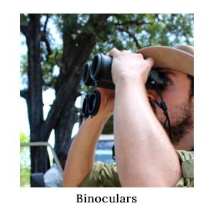 A man wearing a safari hat looking through a pair of binoculars on safari in Africa