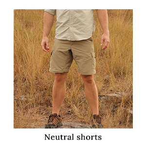 Man in a safari shirt and safari zip-off trousers in ripstop fabric which have been converted into shorts on safari in Africa