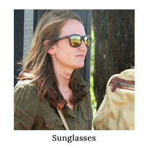 A woman in a safari shirt wearing a pair of Bolle sunglasses to protect her eyes from the sun on a walking safari in Africa