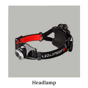 A LedLenser headlamp torch with a black, red, and white elasticated strap for safari in Africa