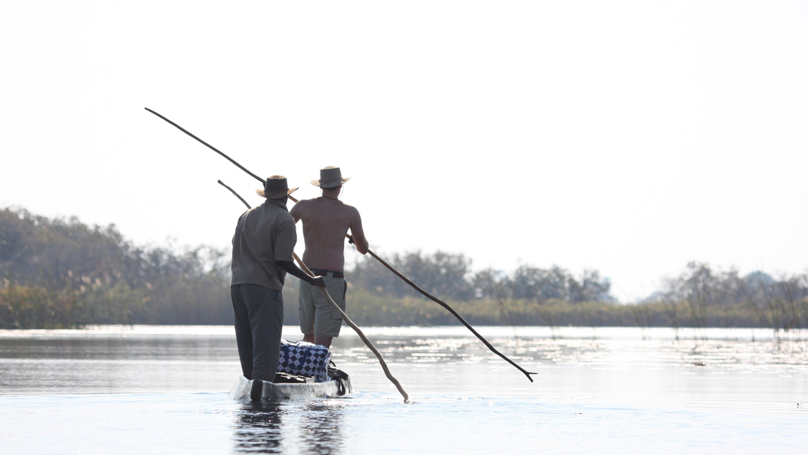Two men wearing safari clothing and hats pole a wooden mokoro in the Okavango Delta river in Botswana.