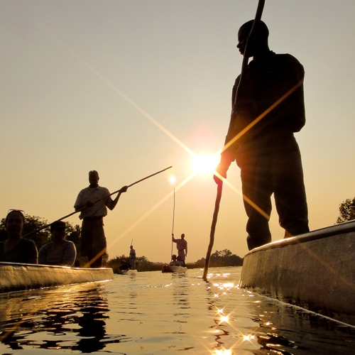 People paddle kayaks on a shimmering river at sunset