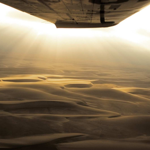 The close-up of the wing of a small plane flying over a golden desert in Africa