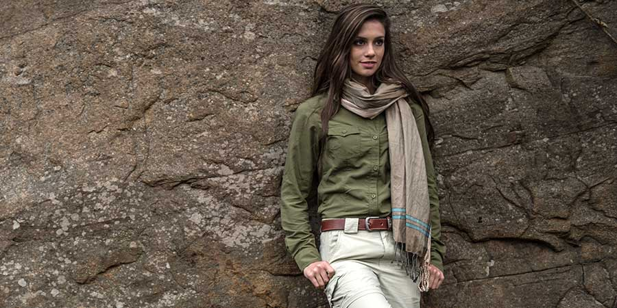 A pretty woman wearing stylish safari trousers, shirt and scarf leans against a rock wall.