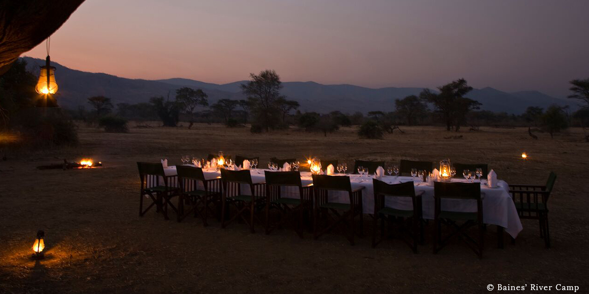 A table set with a white table cloth, hurricane lamps, and camp chairs for a bush dinner on safari at Baines' River Camp