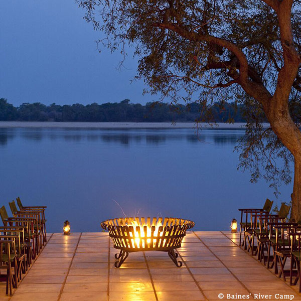 The patio at Baines' River Camp in the evening with camp chairs and lamps around a fire pit overlooking the Zambezi River