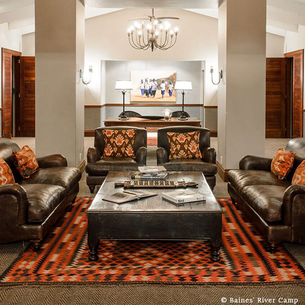 The interior of the luxury safari lodge at Baines' River Camp with leather couches, a wooden table, and ethnic décor