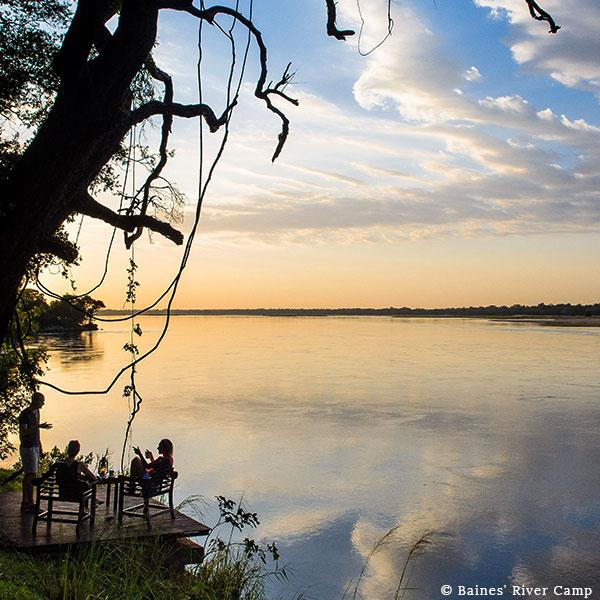 People talking on a wooden platform overlooking the flat Zambezi River on safari at Baines' River Camp, Lower Zambezi, Zambia