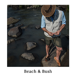 A man in a fishing shirt and outdoor, technical clothing with his fishing rod next to the river on a beach and bush safari