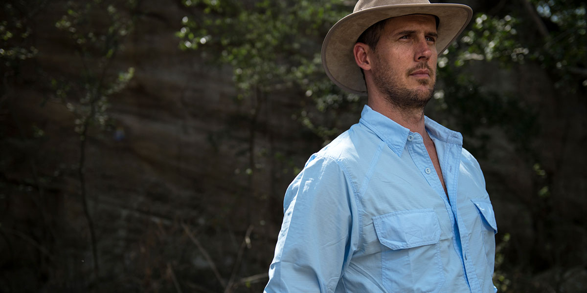 A man in a leather safari hat and a blue travel and outdoor shirt made from insect repellent technical ripstop fabric
